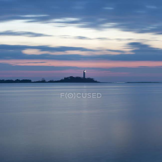 Meereslandschaft mit Leuchtturm in der Abenddämmerung beleuchtet — Stockfoto