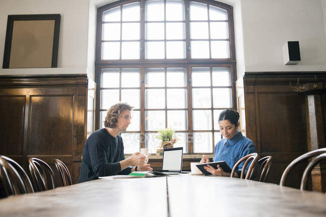 Young freelancers working with laptop and digital tablet in cafe — Stock Photo