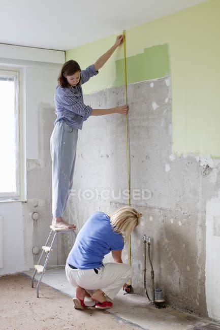 Молоді жінки вимірювання стіни для реконструкції — стокове фото