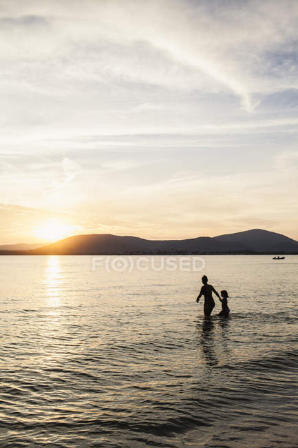 Mother and daughter wading in sea at sunset — Stock Photo