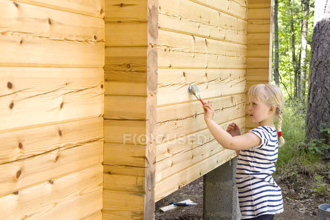 Side view of girl painting built structure — Stock Photo