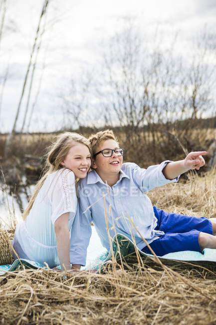 Girl and boy sitting on blanket outside and looking away — Stock Photo