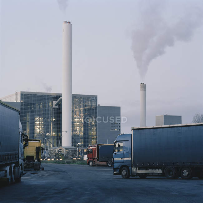 Industrial buildings with pipes and trucks on foreground — Stock Photo