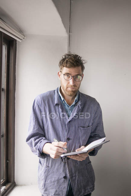 Young man standing by window and writing in notepad — Stock Photo