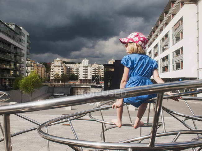 Girl sitting on metal installation, buildings exterior on background — Stock Photo