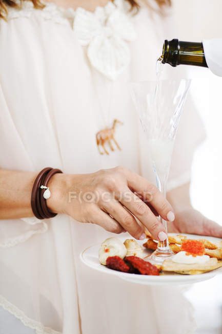 Woman pouring champagne into glass — Stock Photo