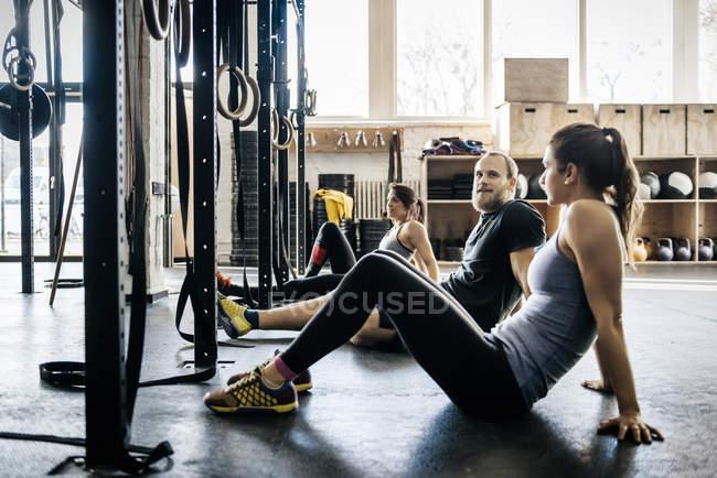 Las mujeres jóvenes y hombre sentado en el piso en gimnasio - foto de stock