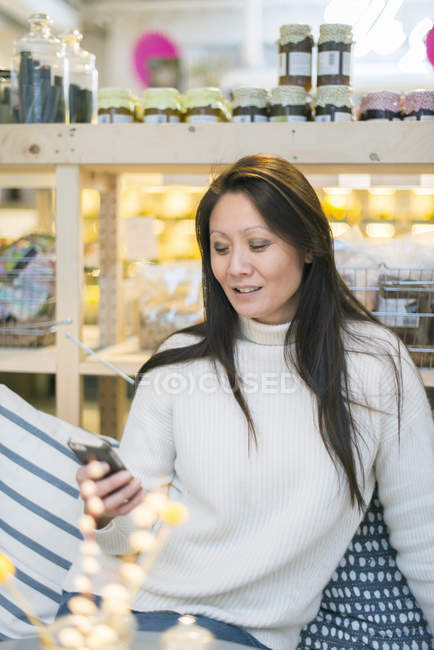 Mature woman using smartphone, differential focus — Stock Photo