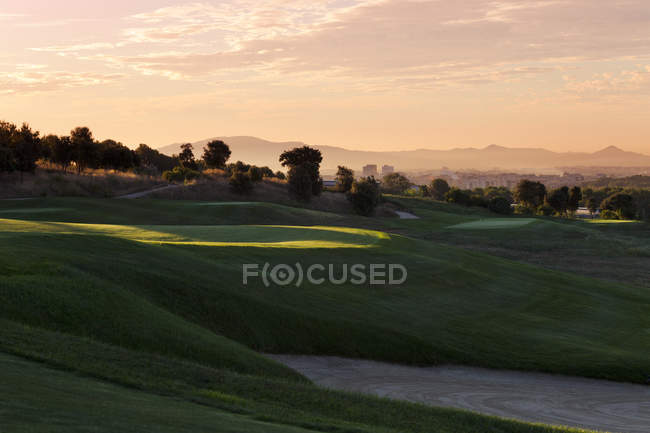 Grassy hills of golf course in shadow with distant cityscape in background — Stock Photo