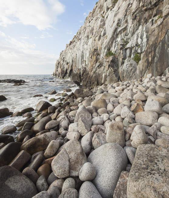 Pierres sur une côte rocheuse avec des vagues de surf — Photo de stock