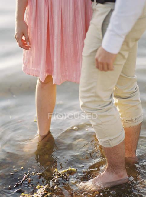 Couples restant pieds nus dans l'eau, foyer sélectif — Photo de stock
