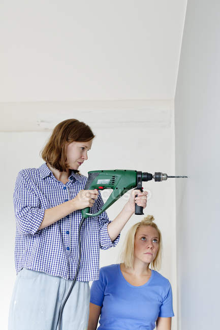 Молода жінка свердлить стіни, зосереджується на розбірливості. — стокове фото
