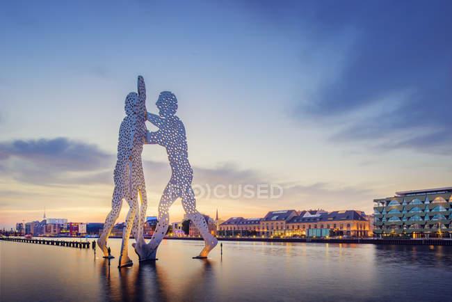 Escultura de hombre molécula en juerga y río iluminado al atardecer - foto de stock