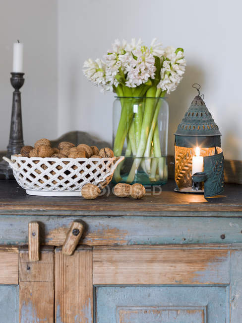 Hyacinths, candles and walnuts on wooden cabinet — Stock Photo