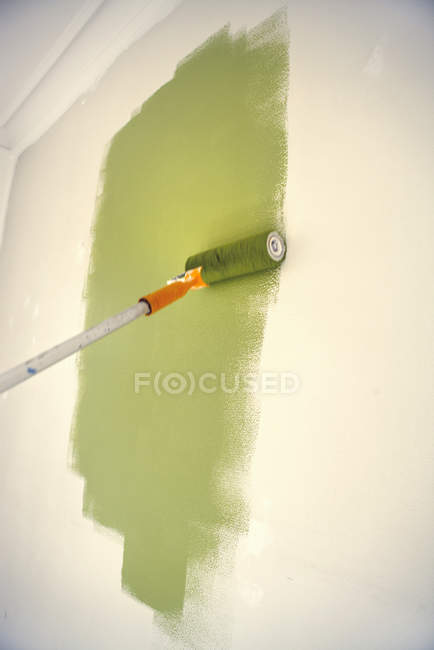 Paint roller with green painting on wall — Stock Photo