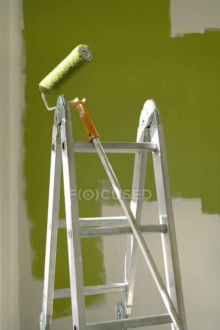 Малярні валики та сходи перед частково пофарбовані стіни — стокове фото
