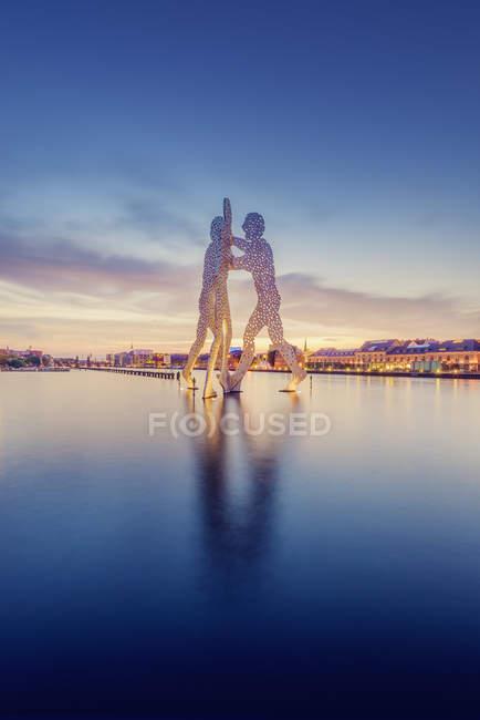 Молекули людина скульптури на Шпрее і освітлену Ріверфронт в сутінках — стокове фото