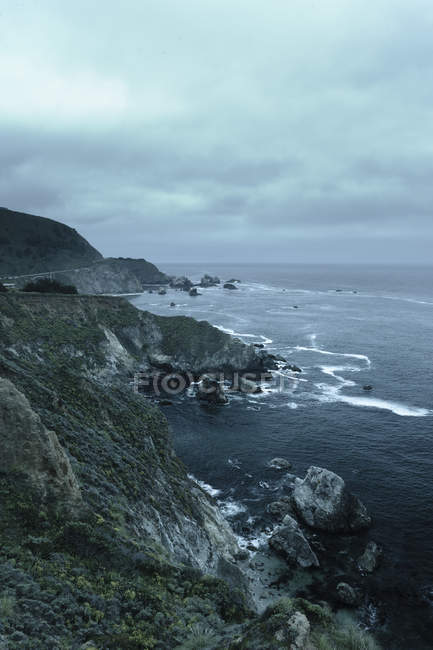 Scenic view of coastline under cloudy sky at dusk — Stock Photo