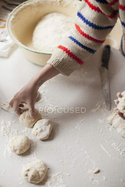 Woman preparing dough on kitchen counter — Stock Photo