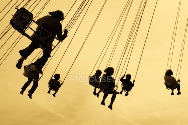 Silhouettes of people on carousel in Liseberg amusement park — Photo de stock