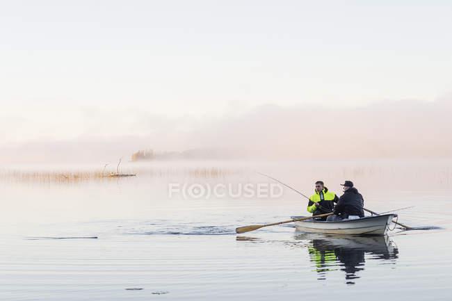 Jovens que pescam no lago ao pôr do sol — Fotografia de Stock
