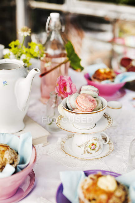 Served table with macarons in cup and teapot — Stock Photo