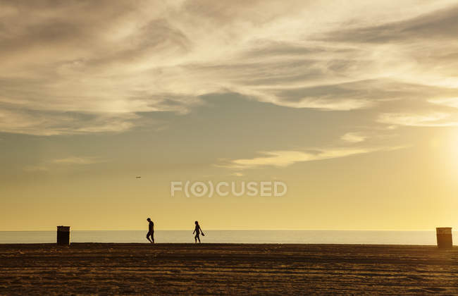 Silhouettes of people walking at sunset by sea — Stock Photo