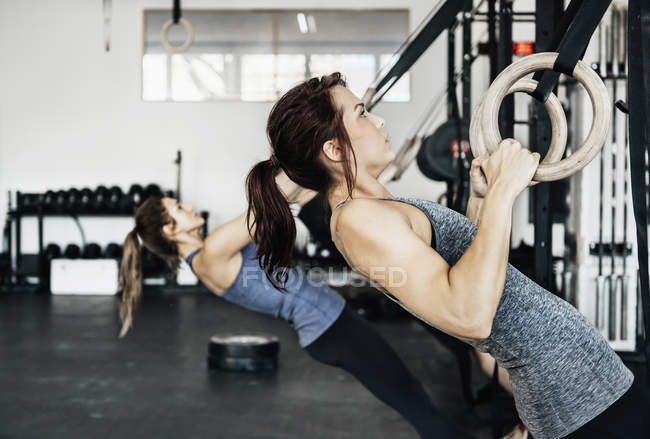 Young women exercising on gymnastic rings — Stock Photo