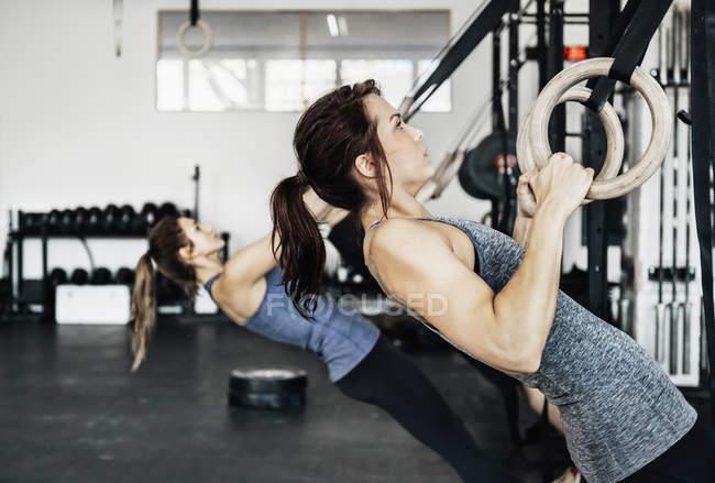 Молоді жінки здійснюють на Кільця гімнастичні — стокове фото