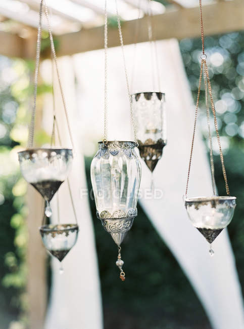 Front view of glass lanterns hanging on chains — Photo de stock