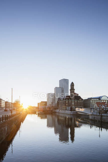 Waterfront cityscape with sunset light and blue sky — Stock Photo