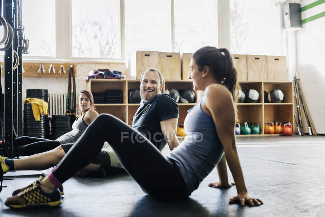 Young women and man sitting on floor in gym — Stock Photo