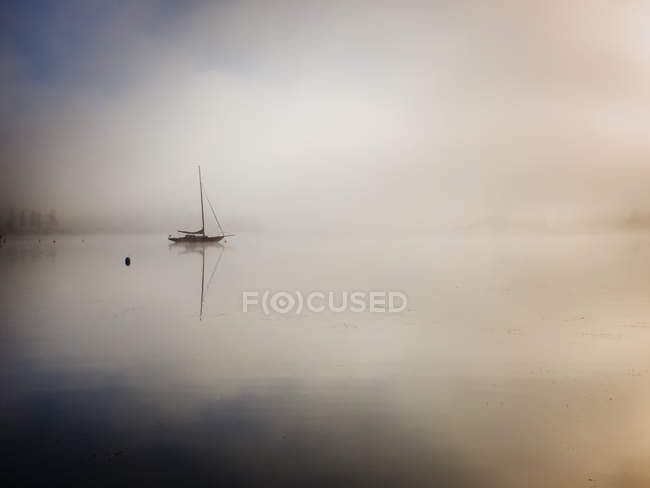 Front view of silhouette of sailboat in fog — Stock Photo