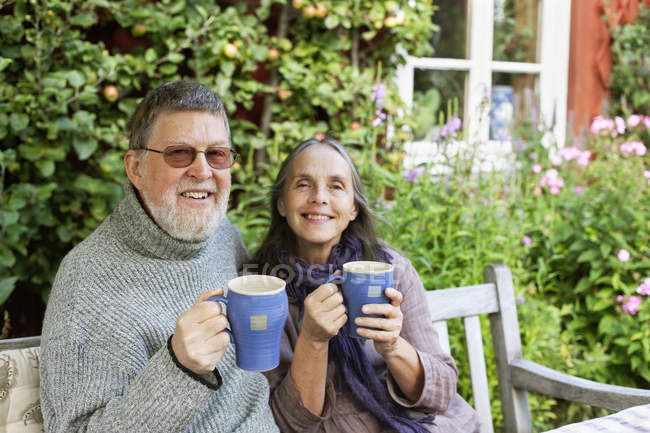 Pareja mayor bebiendo café en el jardín y sonriendo a la cámara - foto de stock