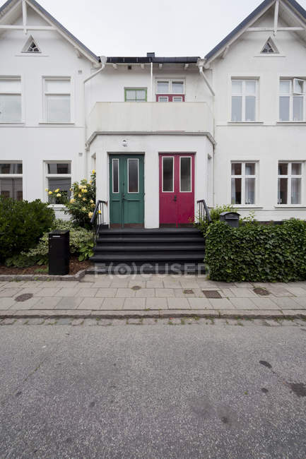 Facade of detached house with two doors and bushes — Stock Photo