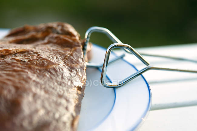 Close up of grilled meat with hooks on plate — Stock Photo