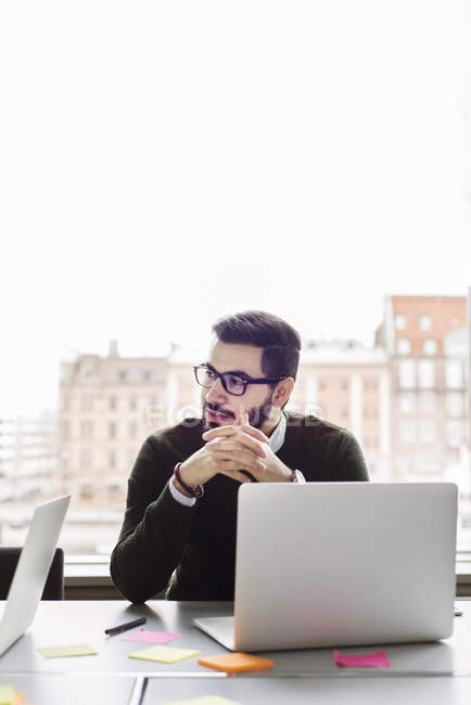 Man sitting with laptop in office and looking away — Stock Photo