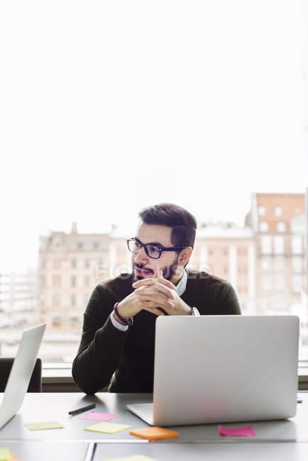Hombre sentado con el ordenador portátil en la oficina y mirando lejos - foto de stock
