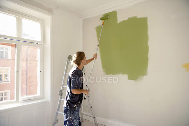 Young man painting wall with paint roller — Stock Photo