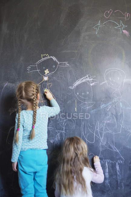 Sœurs dessinant sur tableau, vue arrière — Photo de stock