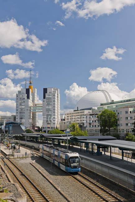 Train beside platform with modern city buildings — Stock Photo