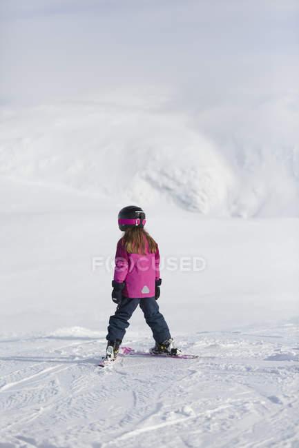 Menina no desgaste do esqui na encosta de montanha — Fotografia de Stock
