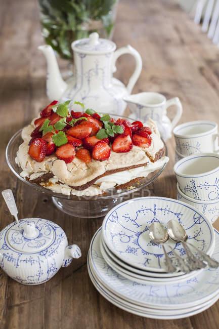 Mesa com xícaras e Pires e morango deserto no cakestand — Fotografia de Stock