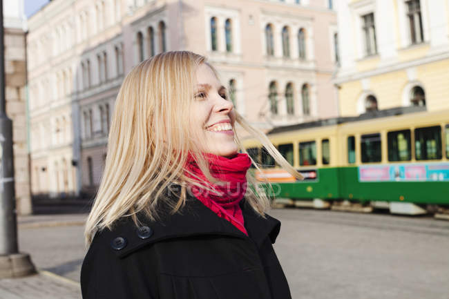 Portrait of laughing woman on town square, focus on foreground — Stock Photo