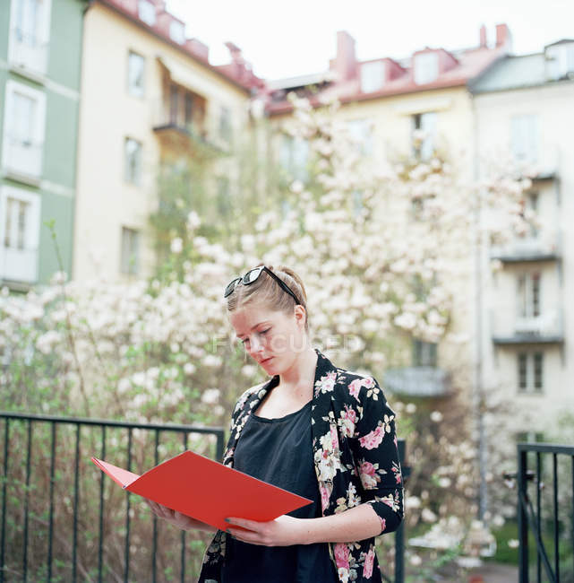 Woman with red folder in residential courtyard — Stock Photo