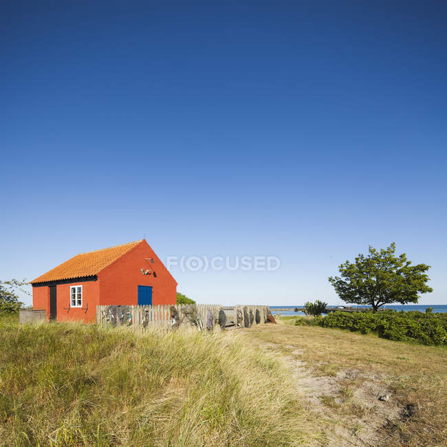 Scenic seascape with red cottage and blue sky — Stock Photo