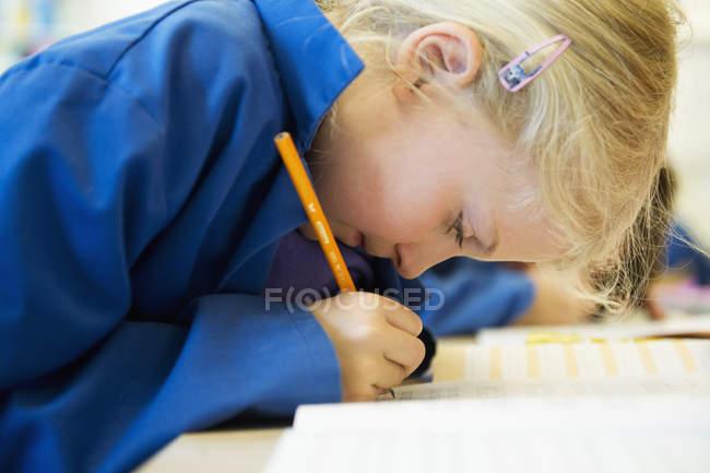 Vista laterale di scrittura della ragazza in aula, fuoco selettivo — Foto stock