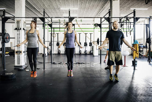 Young women and man skipping rope at gym — Stock Photo