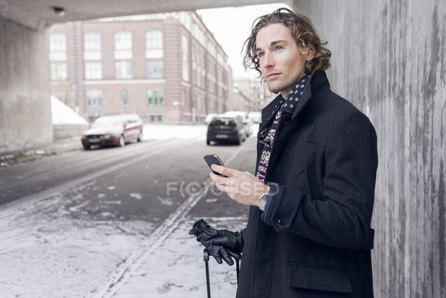 Young man holding smartphone and looking away — Stock Photo