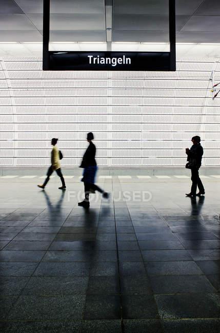 Люди ходят по платформе метро в подсветке — стоковое фото